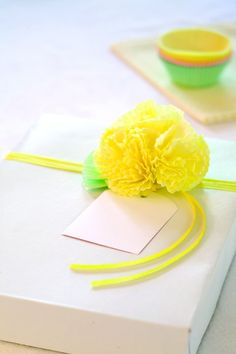 Cupcake Corsage  Create clever bows to finish off your gift boxes using paper cupcake liners. Pinch the liner in the middle from the underside, and pull forward to make a bloom in the shape of a cone. Twist the end to form a stem. Repeat three or four more times, and tape the blooms together to form a flower. Fold green liners flat to mimic leaves