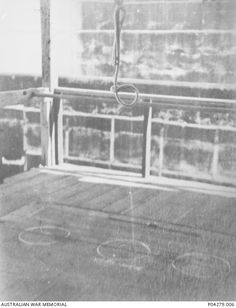 Hangman's noose suspended above the trapdoor of the gallows in Changi Gaol where convicted Japanese war criminals were executed by hanging. The noose is not a traditional hangman's knot but a slip knot and the three circles painted on the trapdoor indicate the positions taken by the condemned during multiple executions. 1946.