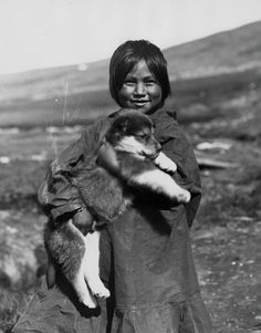 Alfred M. Bailey: Inuit girl with puppy, Alaska, 1922.
