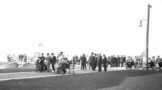 View of people gathered on the boardwalk at Virginia Beach oceanfront with the tunnel to the beach from Seaside Park - Virginia Beach, Virginia. (Date: 1900s - 1910s).