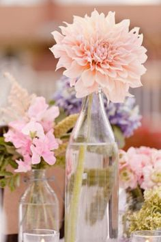 i love the idea of glass bottles and jars as vases for table settings.
