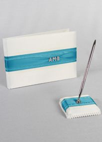 """Stylish white or ivory satin guest book is adorned with layered satin panel in your choice of many David's Exclusive Colors. Three rhinestone monogram charms in the Bride's first name initial, Groom's last name initial and Groom's first name initial add a personalized touch. Comes complete with coordinating pen set.  Features and Facts:  Book dimensions: 9.5"""" W x 6.5"""" H.   Pen base dimensions: 4"""" square.   Pen has silver casing with black ink.  There are 17 total pages in this guest book ..."""