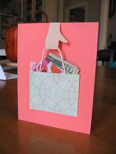 Just glue/double sided tape 3 sides of the 'shopping bag' square so you can later put the cash and money card into the TOP of the square. Tape/glue some string into the INSIDE of the square to make it look like a shopping bag handle. Then with some cream/brown paper cut out the shape of a hand and attach to the string and the card.