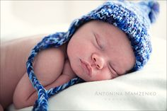 newborn baby baby boy sleeping wearing a blue knitted hat