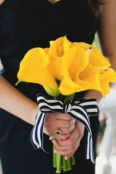 Yellow calla lily bridesmaid bouquet wrapped with a striped ribbon | Brides.com