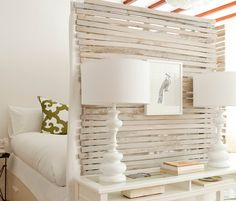 Room divider in bedroom. Wood from crates with lighting, wall hanging, and shelving. Light colored and calm.