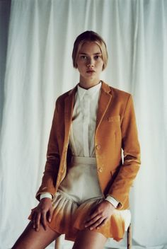 Tan blazer, white collared top, skirt.