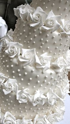 white wedding cake adorned with white pearls and roses