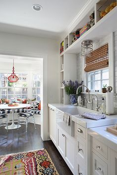 This kitchen with the added breakfast nook is so cute and functional. Loving the lightness of the walls and cabinetry with the pops of color throughout. /ES idea, open shelves, rug, breakfast nooks, color, farmhouse sinks, white cabinets, open shelving, white kitchens