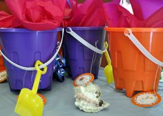 Birthday favors with guppy tags and sea shells on the table.