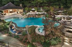 Resembling a tropical resort, this swimming pool and backyard retreat includes an outdoor kitchen, four lounging areas, elevated spa, and waterfall grotto. Lewis Aquatech Pools, Chantilly, Virginia http://www.luxurypools.com/builders-designers/lewis-aquatech-pools.aspx