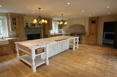 a large french country kitchen with a fireplace and island.