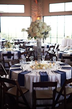 Tall White Rose and Hydrangea Centerpiece | Silver Vase | White Linens | Navy Blue Linens | White Rose Petals | Votive Candles | Premiere Party Central | Omni Barton Creek Resort and Spa | Bouquets of Austin | Fernando Weberich Photography | Pearl Events Austin