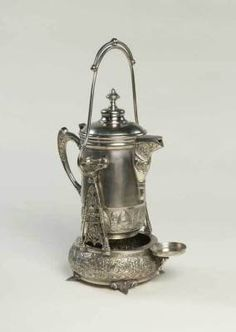 silver tea tipper - Ok, this is just cool....the pot pivots on the base to allow pouring from different angles without lifting a hot pot.  Vintage reproduction.
