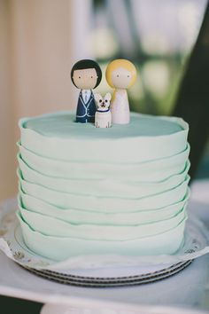 Pleated wedding cake with wooden cake toppers.
