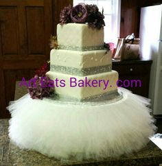 Fabulous 3 tier square off white custom wedding cake with diamond embossing,  rhinestone ribbons,  vintage purple silk flowers and ruffled fabric cake stand.  Art Eats Bakery can create the perfect cake stand to match your dream cake
