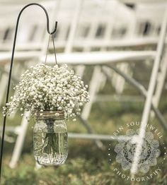 Simple, elegant, and inexpensive aisle marker on shepherd's hook. Mason jar with baby's breath bouquet.
