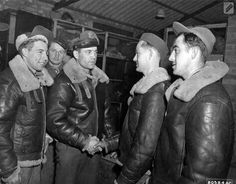 Colonel Joseph Nazzaro of Los Angeles, Calif., Commanding Officer of the 381st Bomb Group at Ridgewell, England, congratulates some of the members of his group who have completed 25 operational missions against the enemy. 18 November 1943