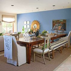 A wash of Pratt & Lambert's Daphne blue brings together an eclectic grouping of a sunburst mirror, wall art and disparate seating. | Photo: Courtesy of Pratt & Lambert | thisoldhouse.com paint color, dine room, din room, placid blue, color concept, blue interior, color trend, blues, accent wall