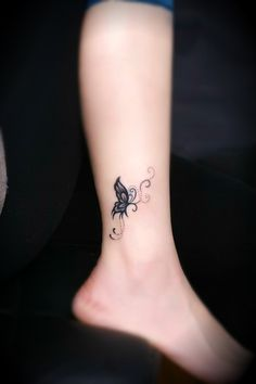 a black tribal type butterfly tattoo near the ankle