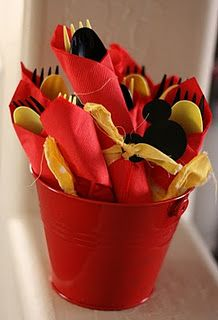 Each utensil bundle has a spoon and a fork of black and yellow and the red napkins were tied with yellow polka dot fabric and a black paper mickey head.