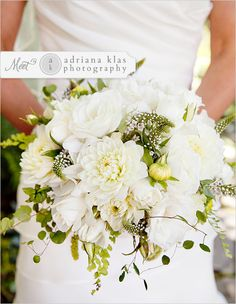 The bride will carry a round textured clutch bouquet of white hydrangea, seasonal greenery, ivory garden roses, ivory dahlias, ivory spray roses, mint green succulents, and queen anne's lace wrapped in burlap with band of lace on top with the stems showing