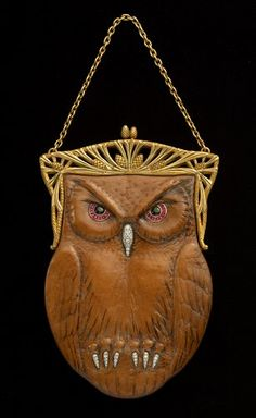 Art Nouveau leather, gold and gem-set ladies evening purse Lacloche Frs. c1905  Frs. Lacloche  The detailed leather bag designed as an Owl with textured detailing back and front and set with banded agate-eyes within a ruby surround and diamond-set beak and claws mounted on an 18ct yellow gold frame with pine cone and needle decoration