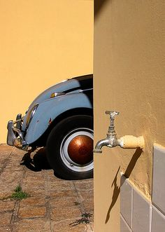 Old beetle & faucet    Not staged. Elements were photographed as found. The golden finish on the hubcap is rust.