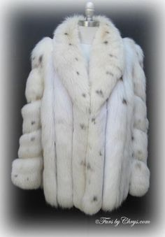 SOLD! White Lynx Dyed Fox Jacket #LF679;   Excellent Condition; Size range: 12 - 16. This is a gorgeous genuine lynx dyed fox fur jacket. It has an Evans Collection label and features a shawl collar, diagonal sleeves and lightly padded shoulders. There are two exterior velvet-lined pockets and one pocket hidden in the lining. The lining is solid taupe and there is an embroidered name monogram. It closes with hooks and eyes. The fur of this lovely jacket is very full, soft and silky. Love!