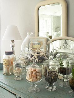 Bring home the beach. Natural sea shells and starfish displayed in glass canisters.