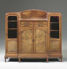 """Eugéne Gaillard (1862-1933) - Vitrine-Cabinet. Carved Walnut and Glass with Bronze Hardware. Circa 1913. 57-1/4"""" x 62-1/2"""" x 16"""" (145.5cm x 158.8cm x 40.6cm)."""