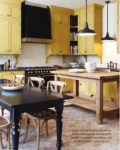 yellow and black kitchen,brick floor, black table