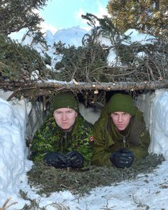 Two members from the Royal Newfoundland Regiment demonstrate a snow shelter they built during Exercise NORTHERN RAIDER at 5 Wing Goose Bay in Happy Valley-Goose Bay, Newfoundland and Labrador, February 24, 2014.