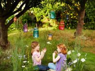 A yard tailored to children doesn't have to mean just swing sets and kiddie pools. Creating a yard or garden children love is all about carving out special spaces where they can let their imaginations soar. This charming  fairy ring you can plant yourself  is one such project. These little girls are enjoying their homegrown fairy ring with their handmade fairy lanterns hanging from overhead tree branches.