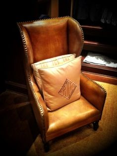 leather wingback chair with monogram pillow.