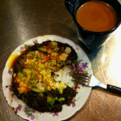 Black frijoles refritos con challots topped with eggs over-medium, avocado, and chipotle salsa; shaped like pacman and a side of coffee.