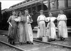 Six unidentified female railroad workers pose at Lincoln Park Station. The railroad line is the Buffalo, Rochester and Pittsburgh Railway Company. In 1917-1918, many jobs traditionally held by men were filled by women, while the men served in the Armed Services in World War I. These women cleaned passenger cars.  [PHOTO: Albert R. Stone Collection]