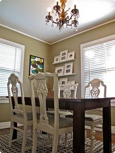 Lovely gray walls, white chairs mixed with dark wood table.