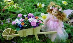 A lovely little fairy wheels a little wheelbarrow full of tiny flowers through the fairy garden.