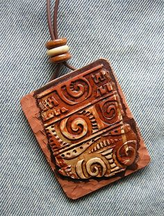 "Belize pendant detail by Pati B. - She says, ""Pendant 2 x 2 1/2  Polymer Clay, wooden beads; antiqued, lightly buffed & waxed. Adjustable bolo closure.  The back panel is comprised of two three thin layers, which are revealed on the sides: cream sandwiched between terra cotta. Initially I had a paper thin linen-textured layer which I stained dark, but then chiseled most of it off, leaving only a suggestion of the linen. The chiseled clay is matte in finish while the fragment has been lightly ..."