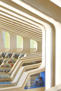 Chunky wooden ribs bend around the walls and ceiling of this library in Norway