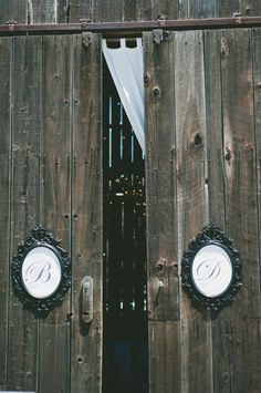 Black framed script initials on barn doors.