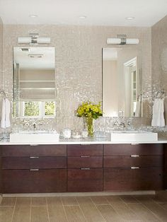Beautiful and functional! Iridescent mosaic glass tile to reflect and brighten lighting. Sleek clean line cabinetry that provides storage and is floating off the floor which I always love!