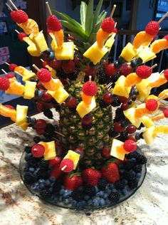 Rainbow fruit kabobs stuck in a pineapple with skewers