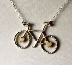 A twist on the classic Le Petit Bike pendant, this little beauty has a loving spin! Two little adorable brass hearts have been soldered to the center of the wheels, giving a playful, individual feel to the necklace. By Rachel Pfeffer.