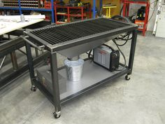 Plasma cutting table with a funnel into metal bucket for catching slag.