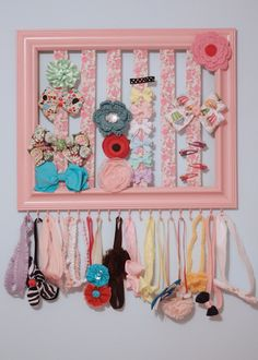 old frame painted with ribbons attached: hair pins on ribbon, head bands hang from hooks on the bottom