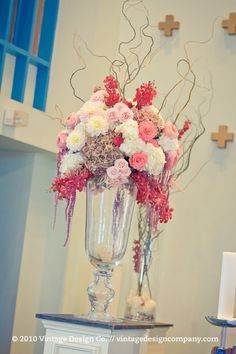 """For the wedding ceremony, we designed a couple of these oversized altar floral arrangements, some pew-posies and filled two of our 42"" glass cylinders with curly willow and red mokara orchids."""