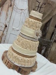 6 tier white almond sour cream wedding cake decorated entirely in latte tinted buttercream icing, accented with burlap ribbon, lace, flower, fondant beads and monogram. Presented on a log slice in venue with rustic, barn decor. Nebraska.