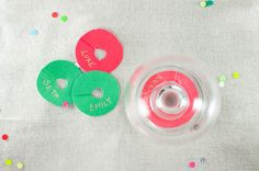 DIY drink tags in holiday colors help your guests keep track of their glasses. Just trace the bottom of a wineglass on a piece of paper and trace a dime in the center. Cut both circles out with a slit between and use your gold pen to label each one.